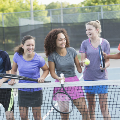 Multi-ethnic teenagers playing tennis.  Girl in middle (17 years, mixed race) is a physically challenged amputee.