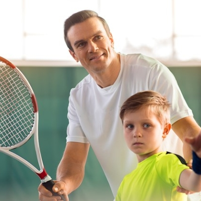 Portrait of happy man teaching son how to hold racquet. He is putting his arms in right position and smiling. Boy is looking forward with concentration