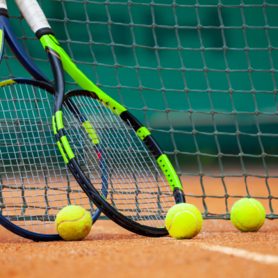 Two tennis rackets and balls leaned against the net.